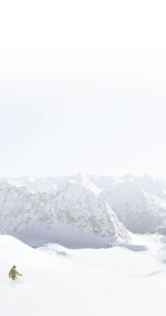 Skifahrer in Tiefschnee vor Alpenpanorama
