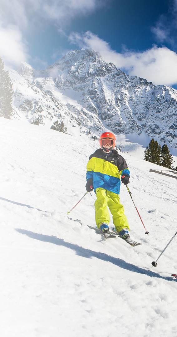 Kinder auf Skipiste vor Bergpanorama